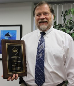 Dr. John Harvey with award