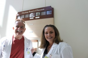 Richard and Melanie Gonzmart pause in front of the Oncology Board of Directors plaque in the UF Small Animal Hospital.