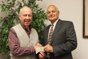 Dr. Paul Nicoletti presents a check to Dean Hoffsis on Jan. 8, 2013.