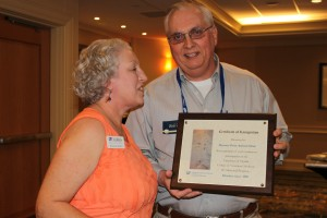 Jo Ann Winn presents a plaque acknowledging support for the Pet Memorial Program to Dr. Robert Hase.